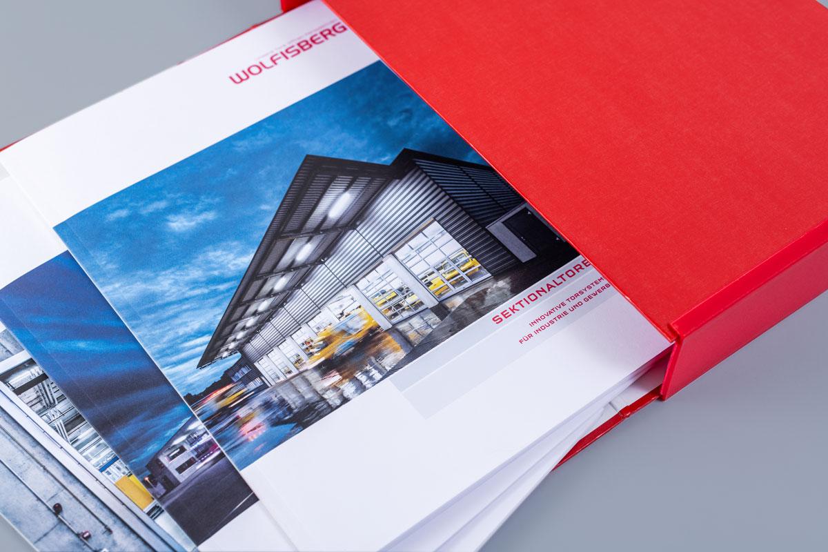 Auswahl von Wolfisberg Broschüren in einer roten Hülle